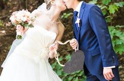 Жених и невеста держа знак сердца форменный Стоковая Фотография