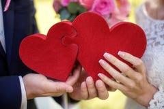 Жених и невеста держа красные сердца головоломки, wedding концепцию, крупный план Стоковые Изображения RF