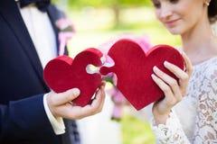 Жених и невеста держа красные сердца головоломки, wedding концепцию, крупный план Стоковые Изображения