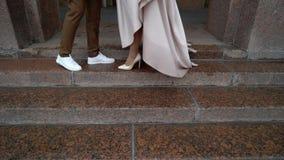 Жених и невеста идя в город на дождливом пасмурном дне Центр европейского городка Новобрачные идя на улицу, платье сток-видео