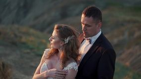 Жених и невеста идя на гору на заходе солнца видеоматериал