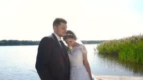 Жених и невеста идя около реки держа руки движение медленное сток-видео