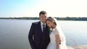 Жених и невеста идя около реки держа руки движение медленное видеоматериал