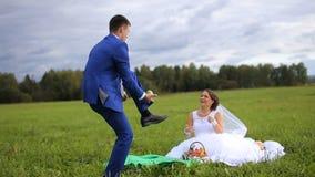 Жених и невеста на зеленом луге в летнем дне акции видеоматериалы