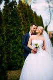 Жених и невеста на дне свадьбы обнимая Outdoors на природе весны Стоковое Изображение RF
