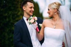 Жених и невеста на дне свадьбы обнимая Outdoors на природе весны Стоковая Фотография RF