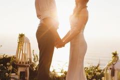 Жених и невеста на предпосылке океана во время захода солнца Стоковые Фото