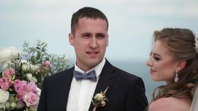 Жених и невеста на свадебной церемонии Молодая пара в стойках любов на своде Свадьба морем сток-видео