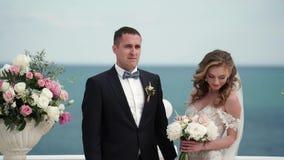 Жених и невеста на свадебной церемонии Молодая пара в стойках любов на своде Свадьба морем видеоматериал