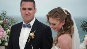 Жених и невеста на свадебной церемонии Молодая пара в стойках любов на своде Свадьба морем акции видеоматериалы
