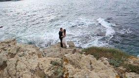 Жених и невеста на скале над океаном сток-видео
