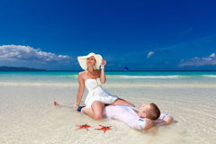Жених и невеста на тропическом береге пляжа с красными морскими звёздами в стоковые фото