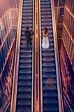 Жених и невеста на эскалаторах стоковая фотография