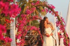 Жених и невеста обнимая около свода цветков в Мальдивах Стоковое Изображение