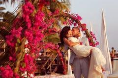 Жених и невеста обнимая около свода цветков в Мальдивах Стоковое Фото