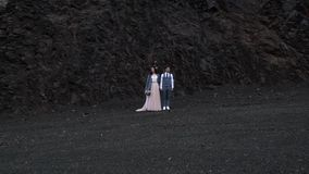 Жених и невеста перед утесом контраста темным Новобрачные держа руки и повернуть вокруг в то же время для взгляда к видеоматериал