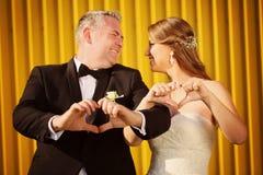 Жених и невеста показывая знак влюбленности с их руками Стоковые Изображения RF