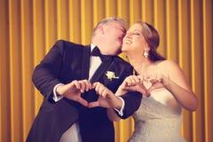 Жених и невеста показывая знак влюбленности с их руками Стоковые Фото