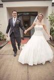 Жених и невеста покидая церковь Стоковые Фото