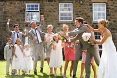 Жених и невеста раскрывая Шампань перед гостями стоковое фото