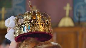 Жених и невеста свадебной церемонии в православной церков церков Заверители держат кроны над головами новобрачных акции видеоматериалы