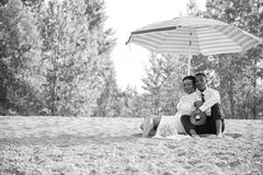 Жених и невеста сидя в песке на пляже под зонтиком стоковые изображения