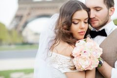 Жених и невеста сидя на стенде в парке, держащ руки одина другого и букета Выхольте держать его голову на плече ` s невесты и Стоковая Фотография