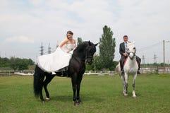 Жених и невеста сидя на лошади стоковые изображения rf