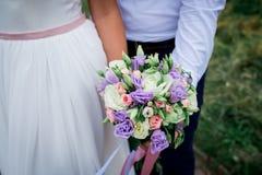 Жених и невеста совместно держа букет свадьбы ювелирные изделия cravat пар кристаллические связывают венчание венчание groom церк Стоковые Изображения RF