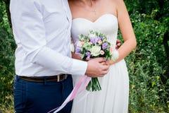 Жених и невеста совместно держа букет свадьбы ювелирные изделия cravat пар кристаллические связывают венчание венчание groom церк Стоковые Фотографии RF