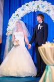 Жених и невеста стоя в своде на свадьбе Стоковое Изображение