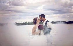 Жених и невеста целуя в тумане Стоковые Фотографии RF