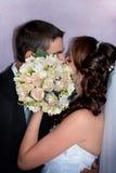 Жених и невеста целуя за букетом свадьбы Стоковые Изображения
