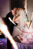 Жених и невеста целуя около свадебного пирога Стоковое Изображение