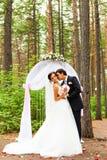 Жених и невеста целуя около свода свадьбы Стоковое Изображение RF