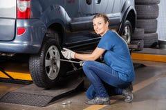 Женская автошина автомобиля отладки механика с ключем оправы Стоковые Фотографии RF