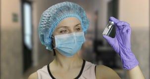 Женская ампула удерживания ученого в руке в больнице, вакцинировании лекарства сток-видео