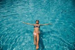 Женская девушка в бассейне кладя на заднюю часть стоковое изображение