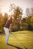 Женская засмолка игрока гольфа к флагу Стоковое Фото