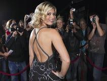Женская знаменитость представляя перед вентиляторами и папарацци Стоковые Изображения RF