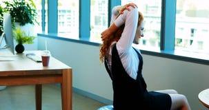 Женская исполнительная власть делая протягивающ тренировку пока работающ на ее столе акции видеоматериалы