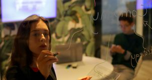 Женская исполнительная власть используя стеклянный цифровой планшет и сочинительство на стеклянной стене 4k акции видеоматериалы