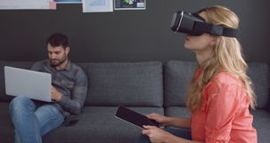 Женская исполнительная власть используя цифровые планшет и шлемофон виртуальной реальности в офисе 4k видеоматериал