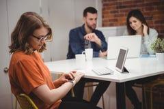Женская исполнительная власть используя smartwatch пока коллеги обсуждая на компьтер-книжке в предпосылке Стоковые Изображения RF