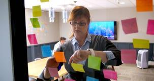 Женская исполнительная власть используя smartwatch пока пишущ на липком примечании на стеклянной стене 4k видеоматериал