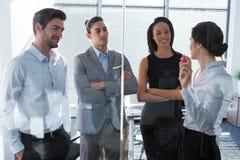 Женская исполнительная власть при его коллеги обсуждая над стеклянной доской Стоковые Фото
