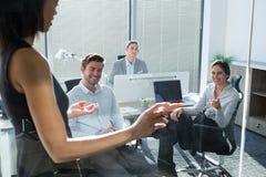 Женская исполнительная власть при его коллеги обсуждая над стеклянной доской Стоковые Фотографии RF