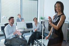 Женская исполнительная власть при его коллеги обсуждая над стеклянной доской Стоковое фото RF