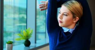 Женская исполнительная власть протягивая ее руки пока работающ в офисе акции видеоматериалы