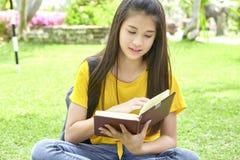 Женская книга чтения подростка в парке стоковое изображение rf